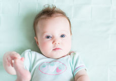 Adorable baby girl on a green knitted blanket smiling Royalty Free Stock Photos