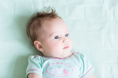 Adorable baby girl in a green shirt on a green knitted blanket smiling Royalty Free Stock Image