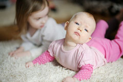 Adorable baby girl and her sister Stock Images