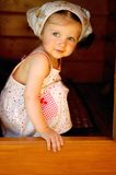 Adorable baby girl hides inside a playground house Royalty Free Stock Photo