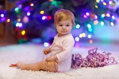 Adorable baby girl holding colorful lights garland in cute hands. Little child in festive clothes decorating Christmas. Adorable baby girl holding pink Christmas royalty free stock photography