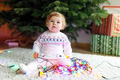 Adorable baby girl holding colorful lights garland in cute hands. Little child in festive clothes decorating Christmas. Tree with family. First celebration of stock images