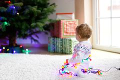 Adorable baby girl holding colorful lights garland in cute hands. Little child in festive clothes decorating Christmas. Tree with family. First celebration of royalty free stock images