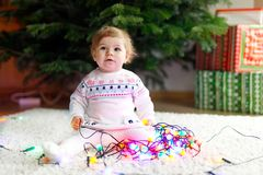 Adorable baby girl holding colorful lights garland in cute hands. Little child in festive clothes decorating Christmas. Tree with family. First celebration of royalty free stock image