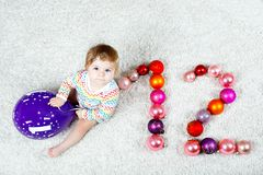 Adorable baby girl holding colorful vintage xmas toy ball in cute hands. Little child and Christmas tree balls as twelve stock images