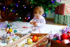 Adorable baby girl holding colorful vintage xmas toy and ball in cute hands. Little child in festive clothes decorating. Christmas tree with family. First stock image