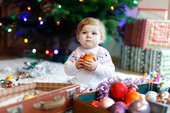 Adorable baby girl holding colorful vintage xmas toys and ball in cute hands. Little child in festive clothes decorating. Adorable baby girl holding colorful stock image