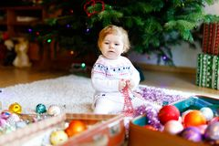 Adorable baby girl holding colorful vintage xmas toys and ball in cute hands. Little child in festive clothes decorating. Adorable baby girl holding colorful stock photos