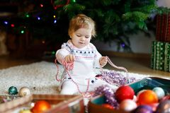 Adorable baby girl holding colorful vintage xmas toys and ball in cute hands. Little child in festive clothes decorating stock photos