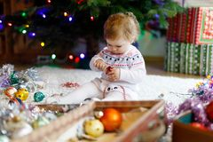Adorable baby girl holding colorful vintage xmas toys and ball in cute hands. Little child in festive clothes decorating royalty free stock photography