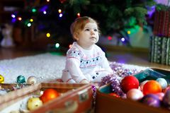 Adorable baby girl holding colorful vintage xmas toys and ball in cute hands. Little child in festive clothes decorating royalty free stock photos