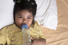 Adorable baby girl holding milk bottle and drinking stock photo