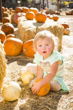 Adorable Baby Girl Holding a Pumpkin at the Pumpkin Patch Stock Images