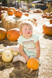 Adorable Baby Girl Holding a Pumpkin at the Pumpkin Patch Royalty Free Stock Images