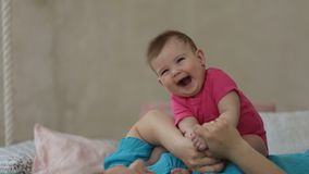 Adorable baby girl laughing in sunny bedroom stock video