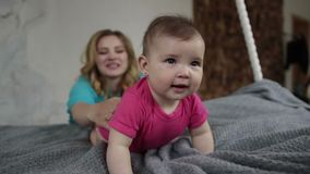 Adorable baby girl learning to crawl on bed stock video footage