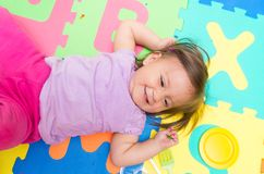 Adorable baby girl lying on floor mats Royalty Free Stock Photo