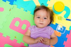 Adorable baby girl lying on floor mats Royalty Free Stock Image