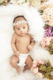 Adorable baby girl lying in fur blanket with flowers around Royalty Free Stock Photo