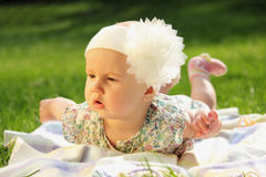 Adorable baby girl lying on green summer grass Royalty Free Stock Photos