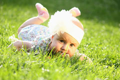 Adorable baby girl lying on green summer grass Royalty Free Stock Image
