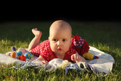 Adorable baby girl lying on green summer grass Stock Images