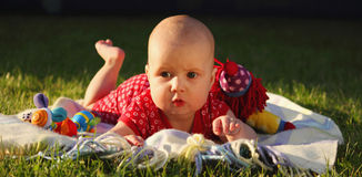Adorable baby girl lying on green summer lawn Stock Photo