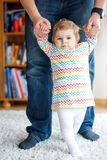 Adorable baby girl making first steps. Father teaching daughter walking. Holding by hands Stock Photography