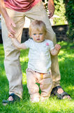 Adorable baby girl making first steps Stock Photo