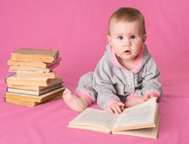 Adorable baby girl with old books reading on pink background. Fo Stock Photography