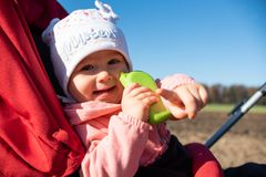 Adorable baby girl outside in red stroller in green fields on a road, sunny day. Baby with green toy pointing finger stock photos