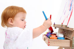 Adorable Baby Girl Painting At Easel royalty free stock photography