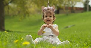 Adorable baby girl at the park dressed as a unicorn.