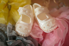 Adorable baby girl pearl shoes just taken out of the box, wrapped in colorful paper royalty free stock images