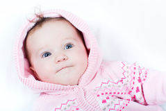Adorable baby girl in pink knitted jacket with red hearts Stock Photo
