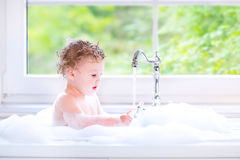 Adorable baby girl playing in big kitchen sink with foam Royalty Free Stock Photos