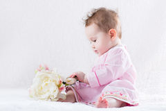 Adorable baby girl playing with a big white flower Royalty Free Stock Image