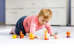Adorable baby girl playing with domestic toy pets like cow, horse, sheep, dog and wild animals like giraffe, elephant. And monkey. Happy healthy child having stock images