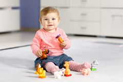 Adorable baby girl playing with domestic toy pets like cow, horse, sheep, dog and wild animals like giraffe, elephant. And monkey. Happy healthy child having stock photography