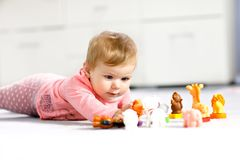 Adorable baby girl playing with domestic toy pets like cow, horse, sheep, dog and wild animals like giraffe, elephant. And monkey. Happy healthy child having royalty free stock photo