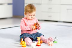 Adorable baby girl playing with domestic toy pets like cow, horse, sheep, dog and wild animals like giraffe, elephant. And monkey. Happy healthy child having royalty free stock image