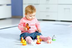 Adorable baby girl playing with domestic toy pets like cow, horse, sheep, dog and wild animals like giraffe, elephant stock photography