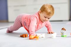 Adorable baby girl playing with domestic toy pets like cow, horse, sheep, dog and wild animals like giraffe, elephant royalty free stock image