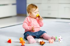 Adorable baby girl playing with domestic toy pets like cow, horse, sheep, dog and wild animals like giraffe, elephant. And monkey. Happy healthy child having royalty free stock photos