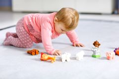 Adorable baby girl playing with domestic toy pets like cow, horse, sheep, dog and wild animals like giraffe, elephant. And monkey. Happy healthy child having stock image