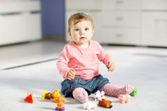 Adorable baby girl playing with domestic toy pets like cow, horse, sheep, dog and wild animals like giraffe, elephant. And monkey. Happy healthy child having stock photo