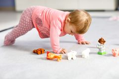 Adorable baby girl playing with domestic toy pets like cow, horse, sheep, dog and wild animals like giraffe, elephant. And monkey. Happy healthy child having royalty free stock photography