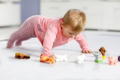 Adorable baby girl playing with domestic toy pets like cow, horse, sheep, dog and wild animals like giraffe, elephant. And monkey. Happy healthy child having royalty free stock images