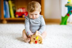 Adorable baby girl playing with educational toys . Happy healthy child having fun with colorful different wooden toy at royalty free stock image