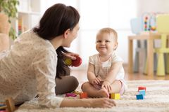Adorable baby girl playing with educational toys in nursery. Child having fun with colorful different toys at home. Nanny or babysitter looks after kid toddler royalty free stock images
